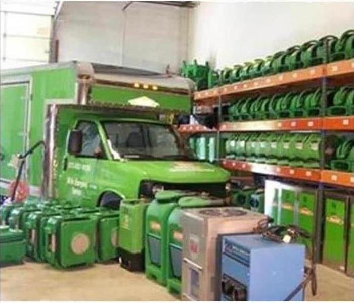 green fans, dehumidifiers and truck in warehouse